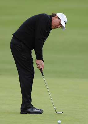 Phil Mickelson putting. His eyes are level over the target line. His feet and body are parallel to it.